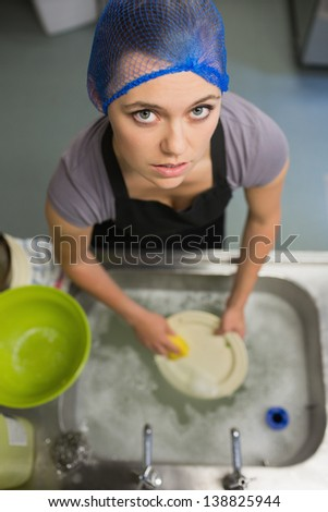 Frowning woman looking up from doing the washing up - stock photo