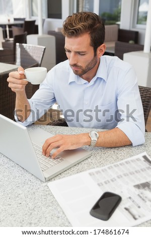 Frowning young businessman using his laptop holding coffee cup in patio of restaurant