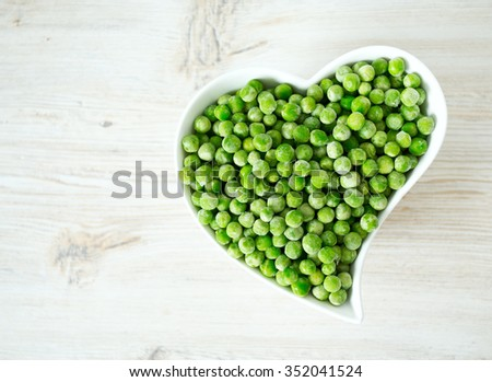 frozem peas on wooden surface - stock photo
