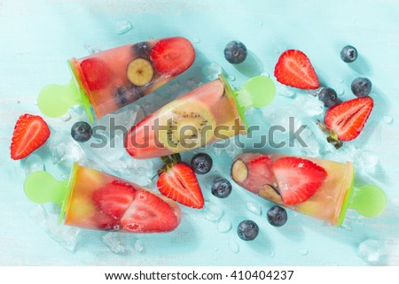 Frozen and iced fruit - strawberry,kiwi, blueberry and coconut water, selective focus