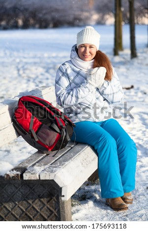Frozen attractive woman sitting on park bench at winter season - stock photo
