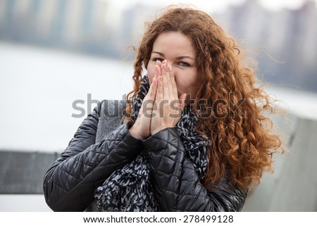 Frozen attractive woman with long curly hair blowing her hands while standing in cold weather - stock photo