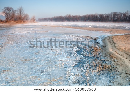 Frozen bank of a misty river in early morning - stock photo