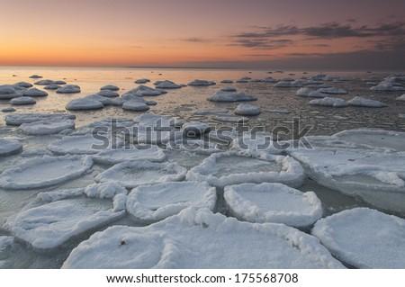Frozen beach after the sunset - stock photo