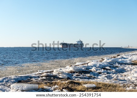 frozen beach near shipyard and sea port with rays of sun and wavebreaker