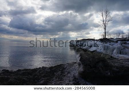 frozen beach overlooking a stormy sky - stock photo