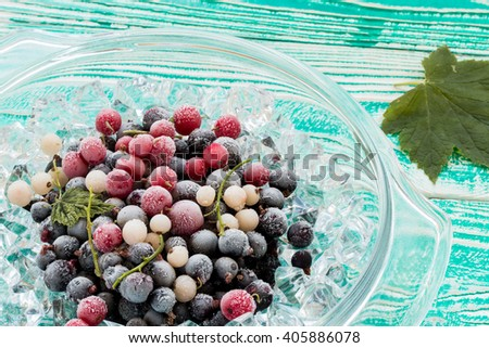 frozen black, red and white  currant berries in glassware with ice crystals  on  turquoise colored wooden table top view - stock photo