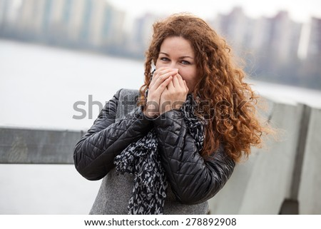 Frozen Caucasian woman with long curly hair warming her hands while standing in the wind on the city street - stock photo
