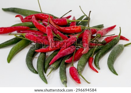 Frozen Chillies.  An assortment of green and red chillies on a white background. - stock photo