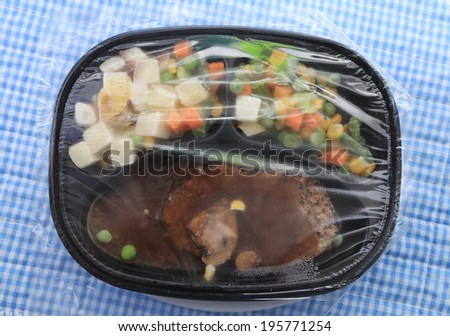 Frozen chopped steak microwave dinner in plastic tray with potatoes and vegetable medley against blue gingham background. - stock photo