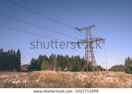 frozen country side by the forest with power lines and blue sky - vintage retro look