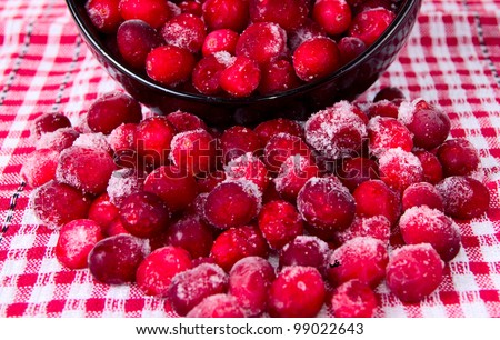 Frozen cranberries on a background of red, checkered tablecloths
