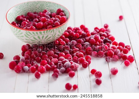 Frozen cranberry in bowl on white wooden background. Selective focus. - stock photo