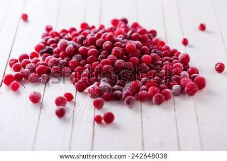 Frozen cranberry on white wooden background. Selective focus. - stock photo