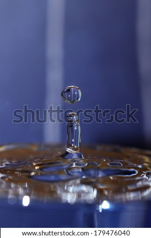 Frozen drop of water, illuminated in different colors. Closeup. Colored background.
