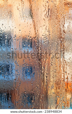 Frozen drops of rain on windowpane at sunset. Bright multi-colored abstract background. - stock photo