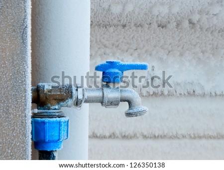 Frozen faucet in winter - stock photo