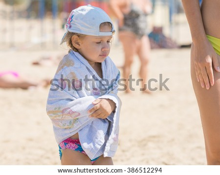 Frozen four-year girl wrapped in a towel standing on the sandy beach sea - stock photo