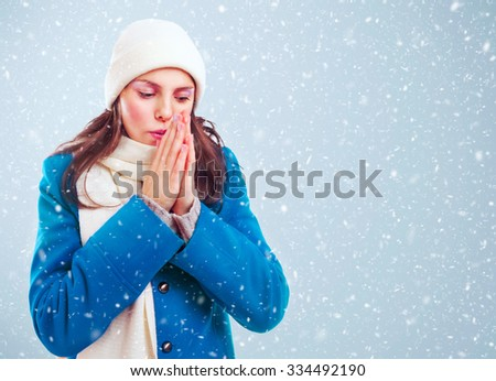 Frozen girl in blue coat, white hat and scarf heats hands among winter snowstorm.  - stock photo