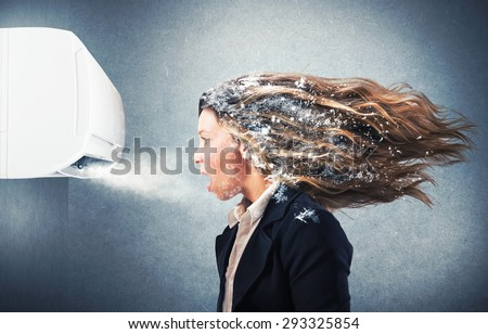 Frozen girl under a powerful air conditioner - stock photo