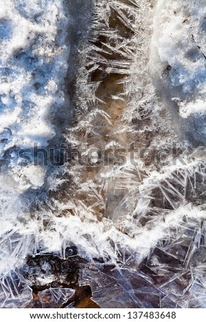 frozen ice crystals under melting snow stream in spring forest - stock photo