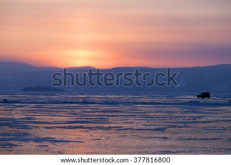 Frozen Lake Baikal. in sunset time with car in the background - stock photo