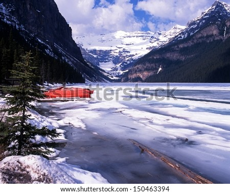 Frozen Lake Louise with snow capped mountains to the rear, Alberta, Canada - stock photo