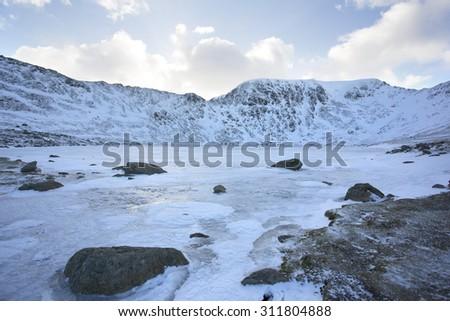 frozen lake overlooking mountain range at sunset, helvellyn, cumbria - stock photo
