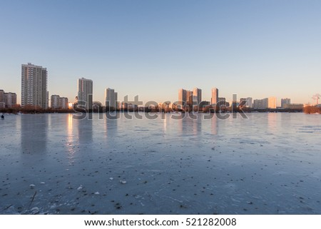 Frozen lake reflecting buildings and sky