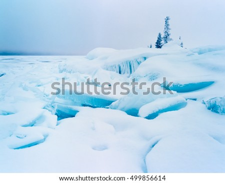Frozen lake shore winter landscape of jumbled ice floes and white snow cover on grey midwinter day