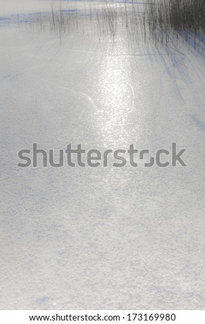 frozen lake - sun reflecting in the surface of ice - stock photo