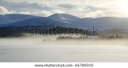 Frozen lake with mist in the distance. (Loch Morlich, Scottish Highlands. This area is in the Cairngorm National Park.)