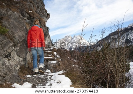 Frozen lake - Woman walking by a frozen lake with famous German mountain in the background - stock photo