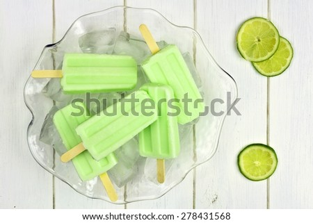 Frozen lime yogurt popsicles in an ice filled bowl against a white wood background - stock photo