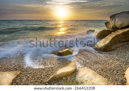 Frozen moment wave enveloping the stone on the seashore - stock photo