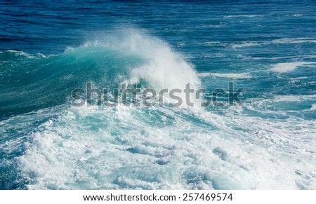 Frozen motion of large wave or breaker approaching shore and short shutter speed freezing the water into droplets - stock photo