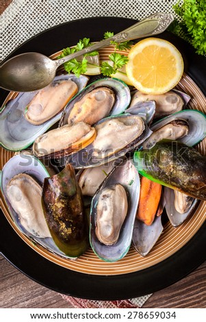 Frozen mussels in shells on the plate. - stock photo