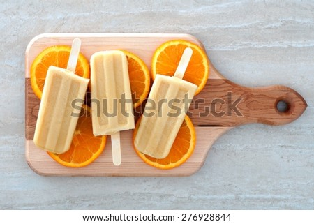 Frozen orange flavored yogurt pops with fruit slices on a wooden paddle board - stock photo