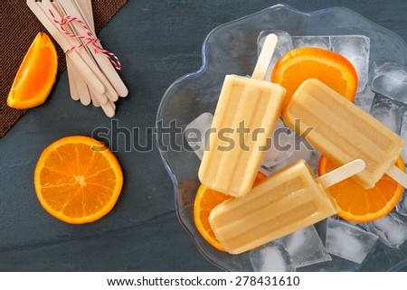 Frozen orange yogurt popsicles in an ice filled bowl with fresh fruit slices against a slate background - stock photo