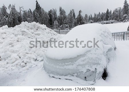 Frozen parked car with icicles, ice and frost covered with snow - stock photo