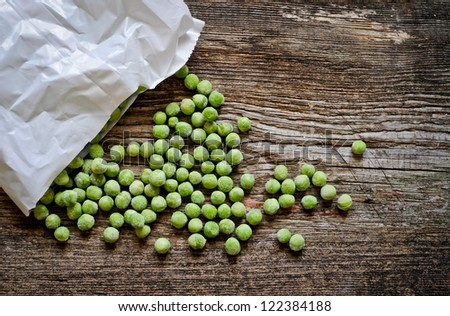 frozen pea on an old wooden table - stock photo
