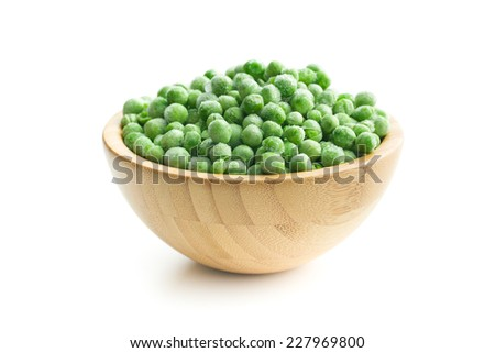 frozen peas in wooden bowl - stock photo