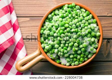 frozen peas on kitchen table - stock photo