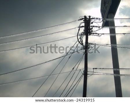 Frozen power lines right after the ice storm ended in Paducah. The sun is making its first appearance through the mean looking clouds. - stock photo