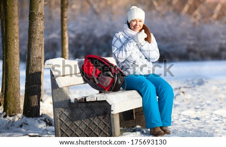 Frozen pretty woman with backpack sitting on park bench at winter season - stock photo