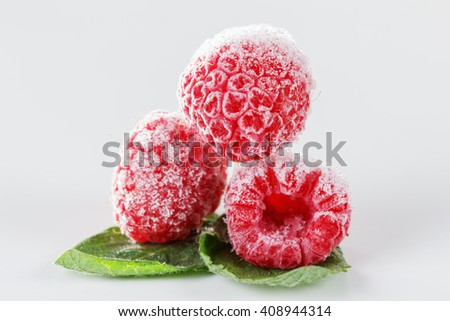 Frozen raspberries with mint leaves on white - stock photo