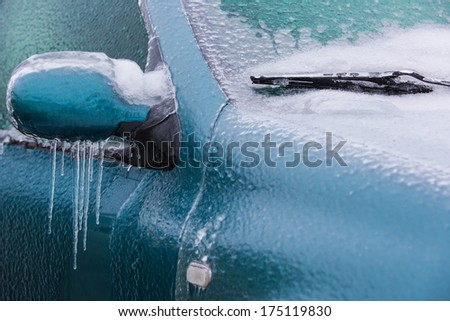 Frozen rearview mirror and wiper of the car with icicles, ice and frost - stock photo