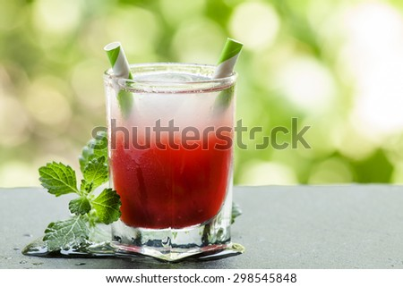 Frozen red cocktail with mint on the sun deck on a summer day, selective focus - stock photo