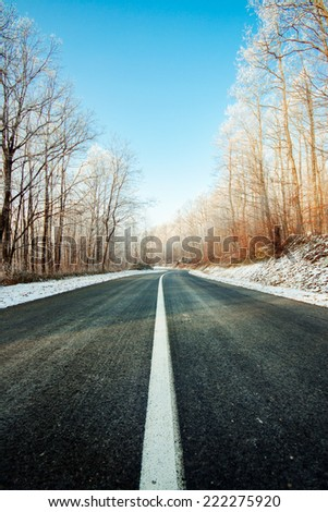Frozen road on a sunny winter day - stock photo