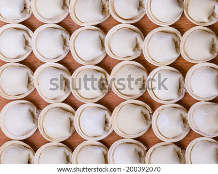 Frozen russian crude pelmeni as a food background or texture - stock photo